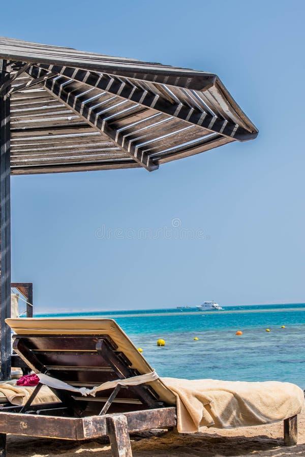 Deckchair pod słońce parasolem na plaży zdjęcie stock
