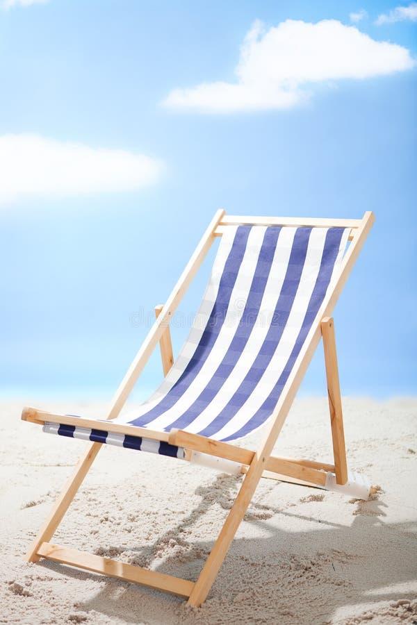Deckchair que se coloca en la playa asoleada imagen de archivo libre de regalías