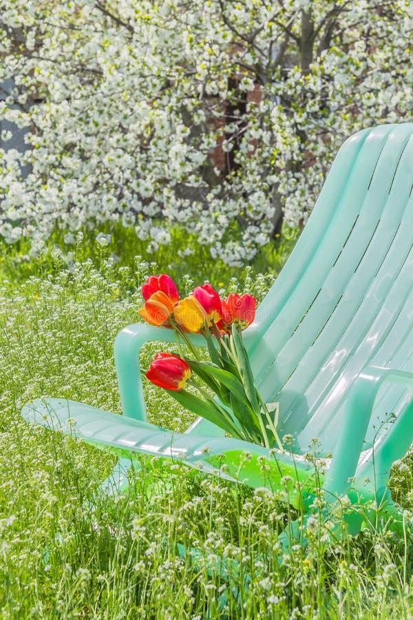 Deckchair und ein Blumenstrauß von Tulpen im Garten lizenzfreies stockbild