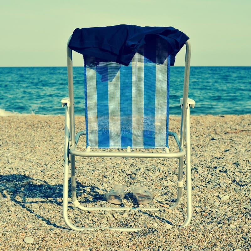 Deckchair und Mannbadeanzug auf dem Strand, mit einem Retro- Effekt stockfoto