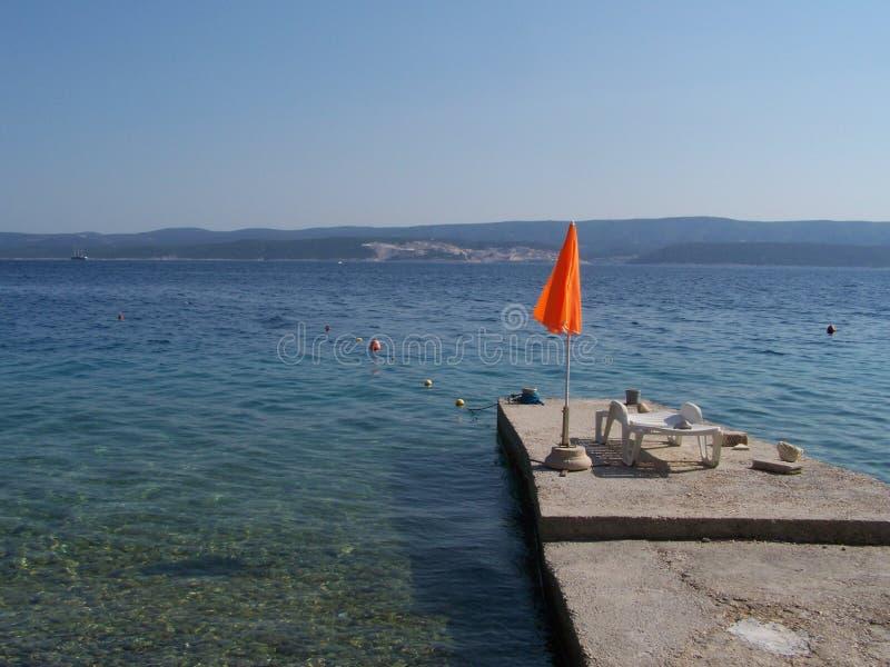 Deckchair und Sonnenschirm auf dem Pier lizenzfreies stockbild