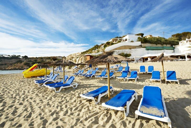Deckchair und Sonnenschutz auf einem Strand von ibiza lizenzfreie stockbilder