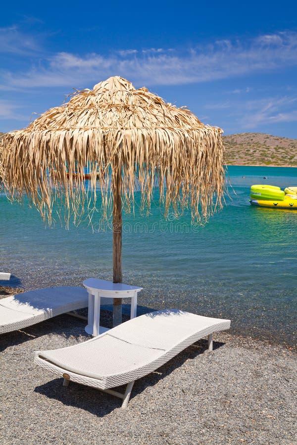 Deckchair unter Sonnenschirm in Ägäischem Meer lizenzfreie stockfotografie