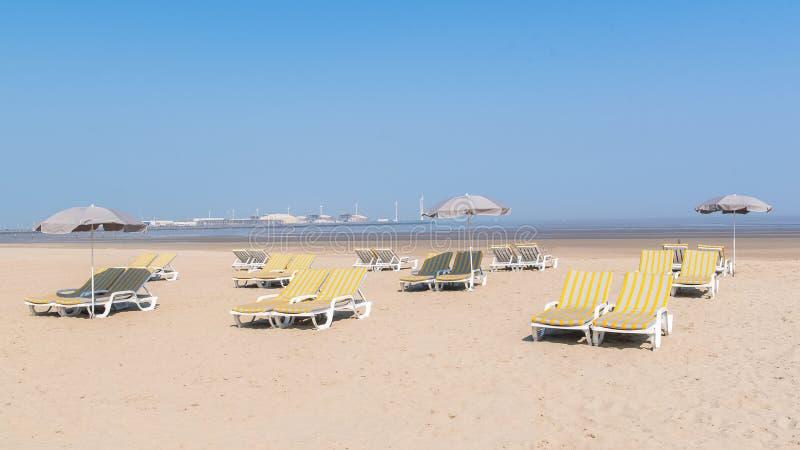 Deckchairs и парасоли на пляже стоковое фото