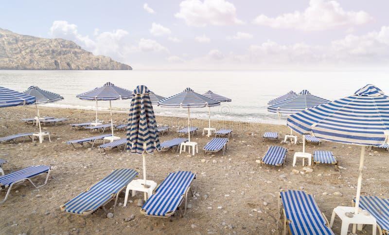 Deckchairs и парасоли на пустом пляже стоковые фото