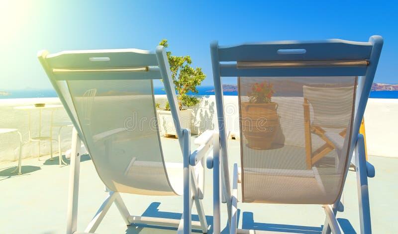 2 deckchairs на крыше здания на острове Santorini, Греции Взгляд на кальдере и Эгейском море, солнечном дне, голубом небе стоковая фотография rf