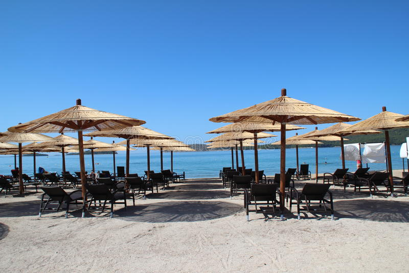 Deckchairs and beach umbrellas on a croatian beach royalty free stock photography