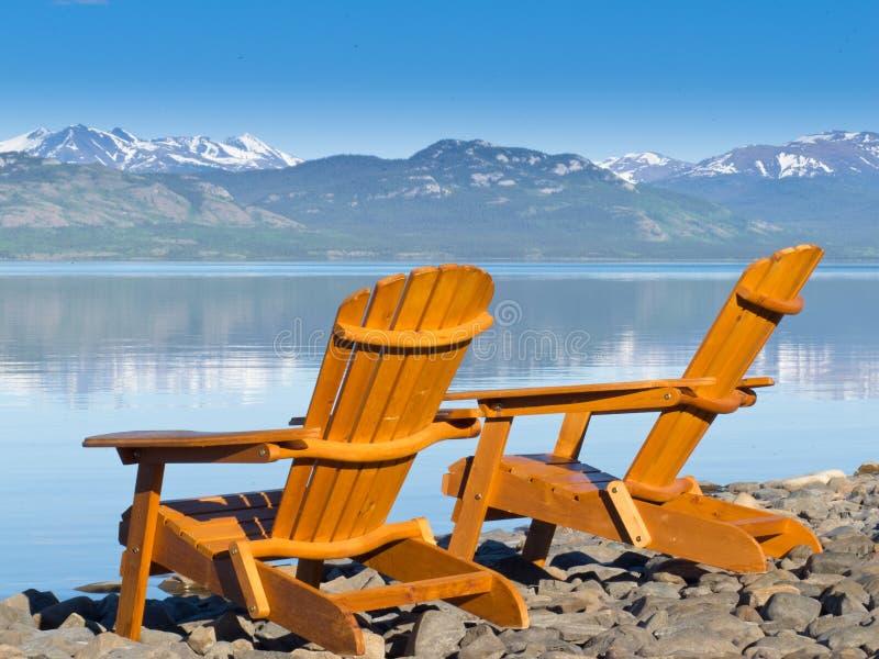 Deckchairs en bois donnant sur le lac scénique Laberge photo libre de droits