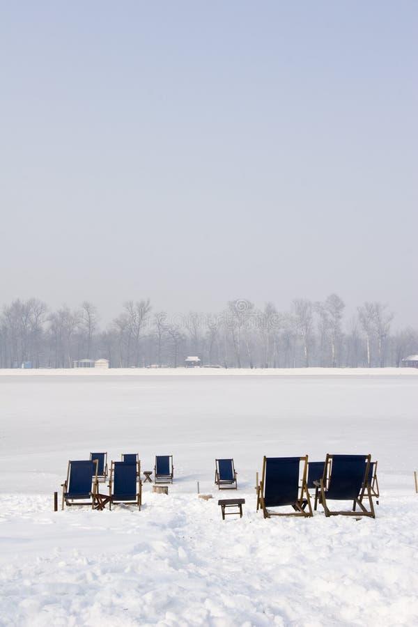 Deckchairs en un lago congelado foto de archivo