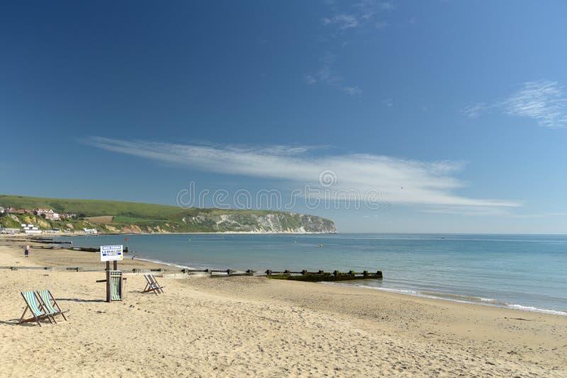 Deckchairs i widok nad zatoką od Swanage wyrzucać na brzeg zdjęcia royalty free