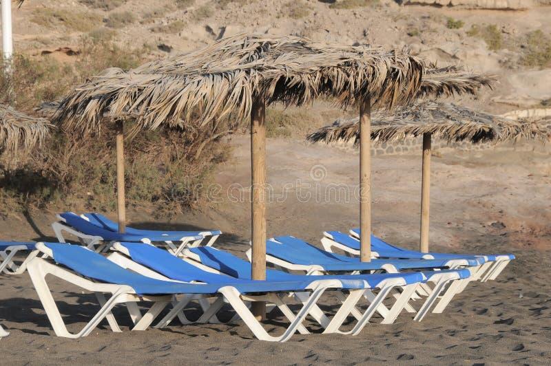 Deckchairs op een Eenzaam Woestijnstrand stock afbeeldingen