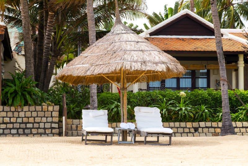 Deckchairs, paraplu en stoel, parasol op het tropische zandstrand stock fotografie