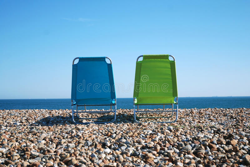 Download Deckchairs on pebble beach stock photo. Image of pebble - 9831546