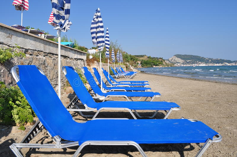 Deckchairs and sunshades. Sunbeds and umbrellas on a small beach. Zakynthos - Greece stock images
