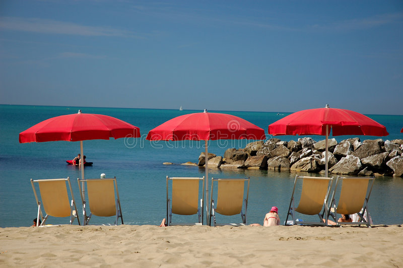 Deckchairs with sunshades on the beach stock photo