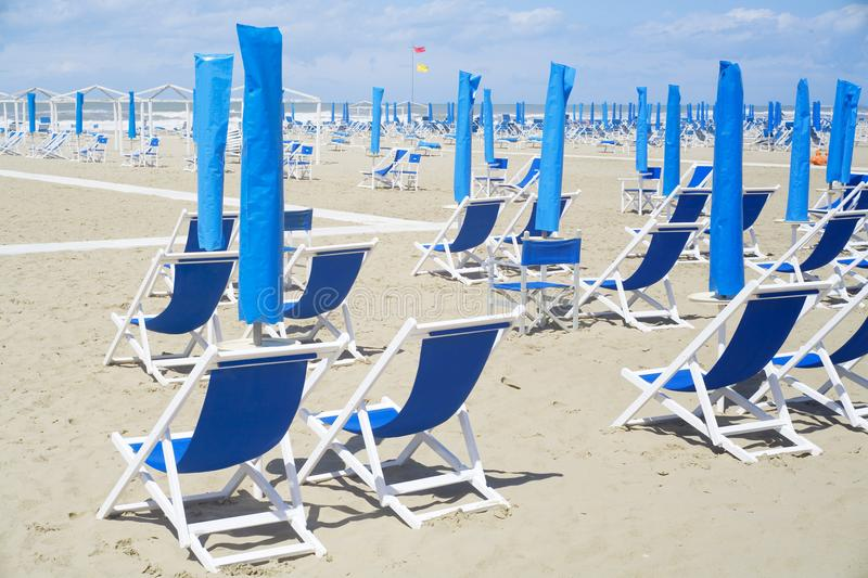 Deckchairs and sunshades on the beach royalty free stock photography