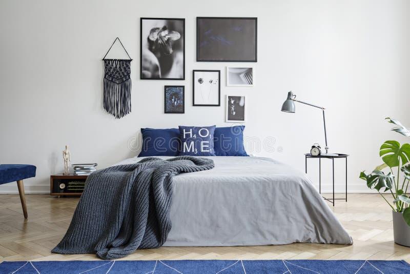 Decke auf Bett mit blauen Kissen im weißen Schlafzimmerinnenraum mit Galerie und Lampe auf Tabelle Reales Foto stockfoto