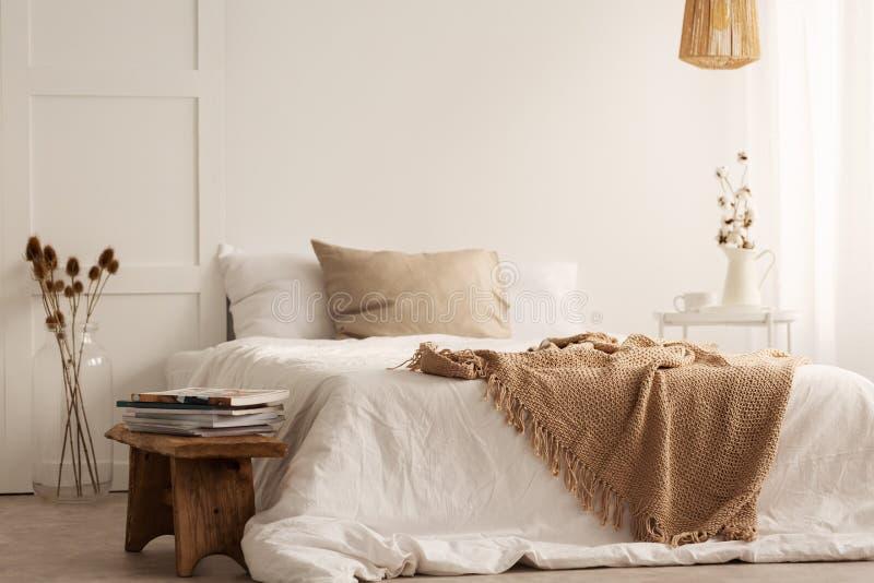 Decke auf weißem Bett im natürlichen Schlafzimmerinnenraum mit Anlagen und hölzernem Schemel lizenzfreies stockbild