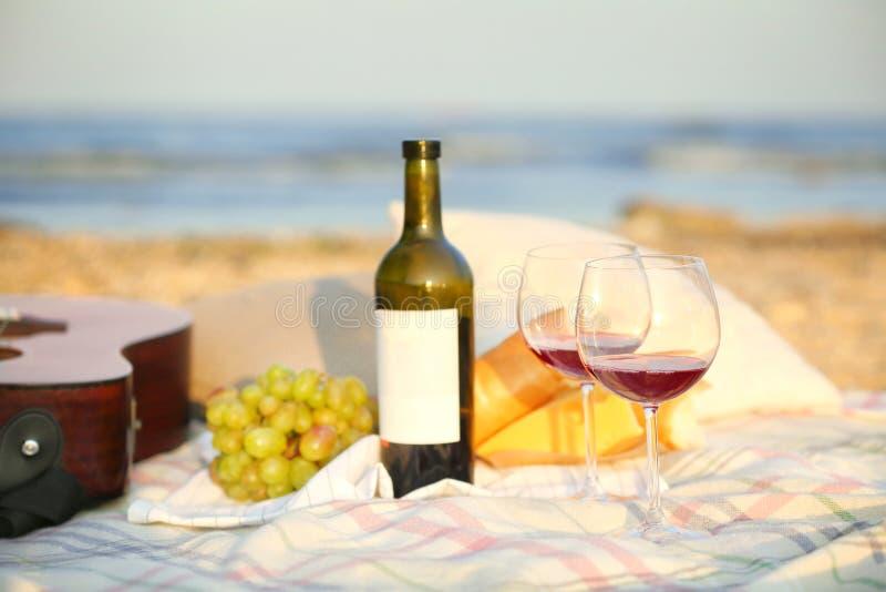 Decke mit Lebensmittel, Wein und Gitarre stockfotografie