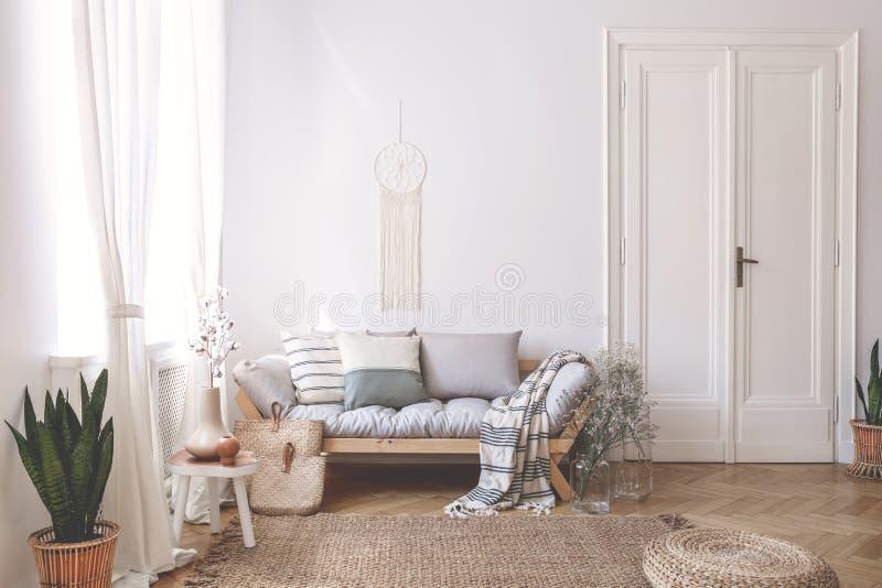 Decke und Kissen auf hölzernem Sofa im weißen Dachbodeninnenraum mit Puff und Anlage auf Teppich Reales Foto lizenzfreie stockbilder