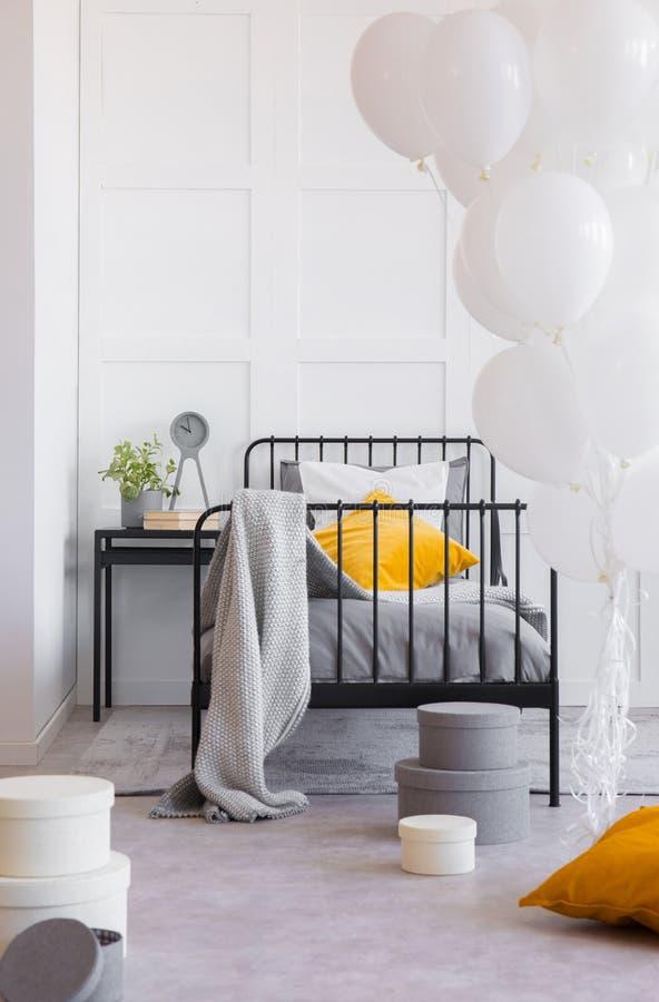 Decke und orange Kissen auf Bett im Innenraum mit Ballonen Reales Foto lizenzfreie stockfotos