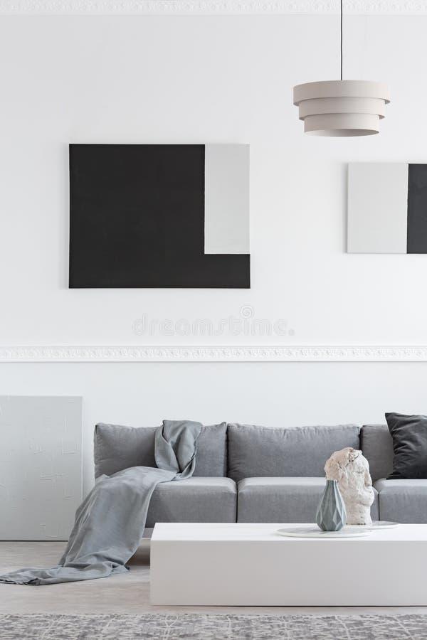 Decke und schwarzes Kissen auf bequemem Sofa im stilvollen Wohnzimmerinnenraum stockfotografie