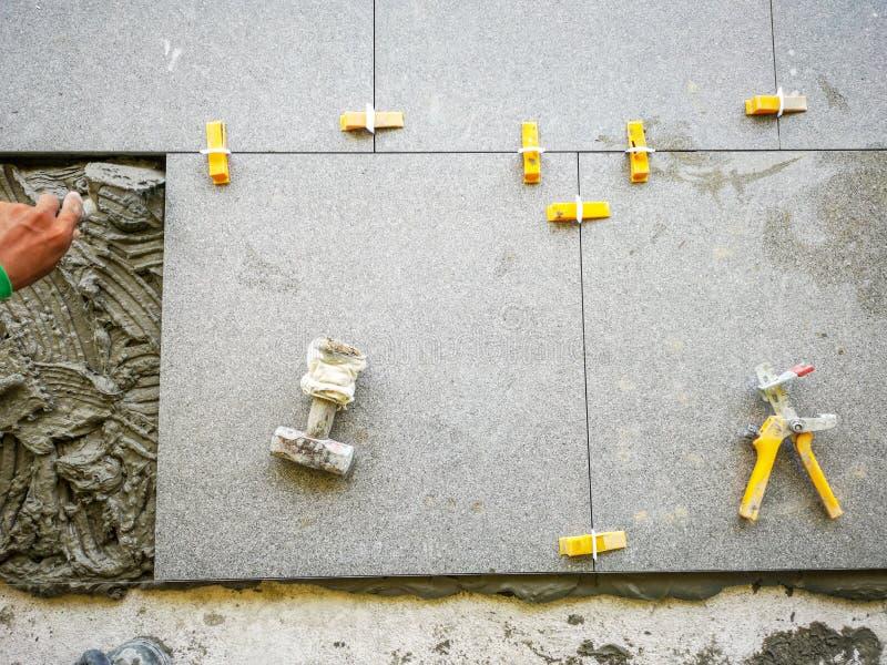 Decken Sie die Arbeit mit Ziegeln, die herein keramische Bodenfliese mit der Peitschenfliese setzt, die System planiert stockbild
