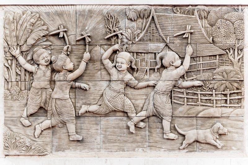 Decken Sie Steincarvingsbild traditionelles Spiel des Bambuslibellen-Spielzeugs, Handwerk für thailändische Kinder mit Ziegeln stockbilder