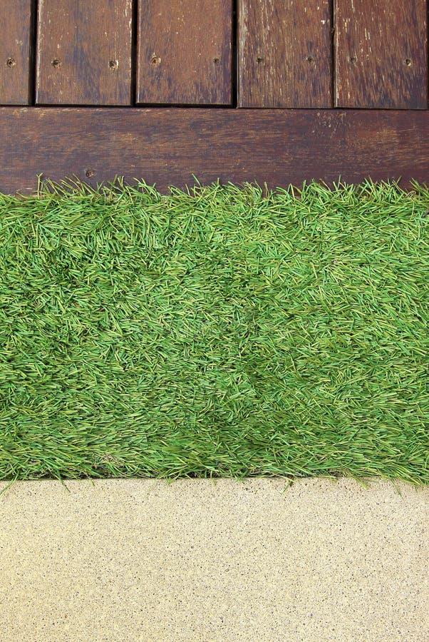 Decking concreto de la madera del piso e hierba artificial verde imagen de archivo libre de regalías