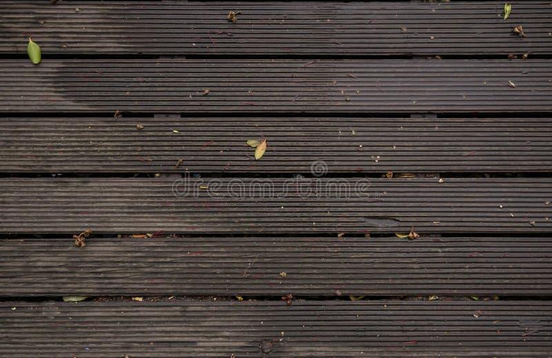 Decking de madera mojado después de una ducha de lluvia con agua, las hojas y las ramitas foto de archivo libre de regalías