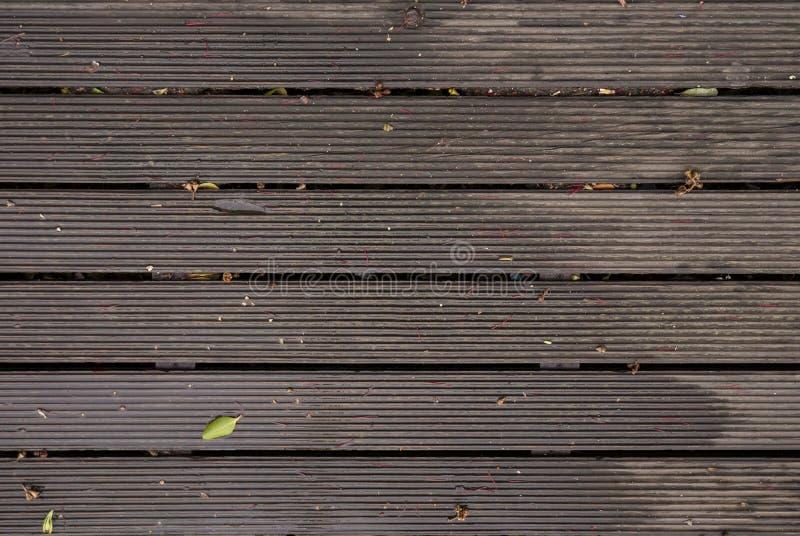 Decking de madera mojado después de una ducha de lluvia con agua, las hojas y las ramitas imagen de archivo