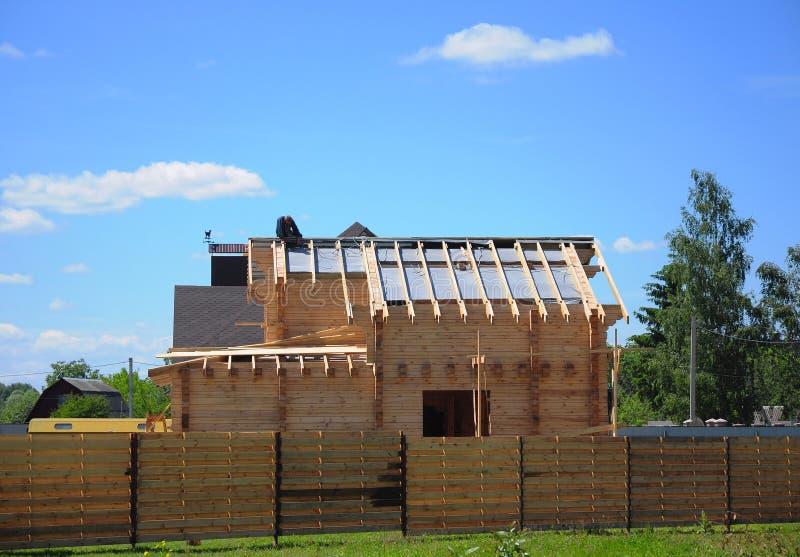 Deckungs-Bau-und Gebäude-neues Holzhaus-Äußeres Erbauer, Roofer Install, Reparatur Asphalt Shingles auf der Dachspitze lizenzfreies stockfoto