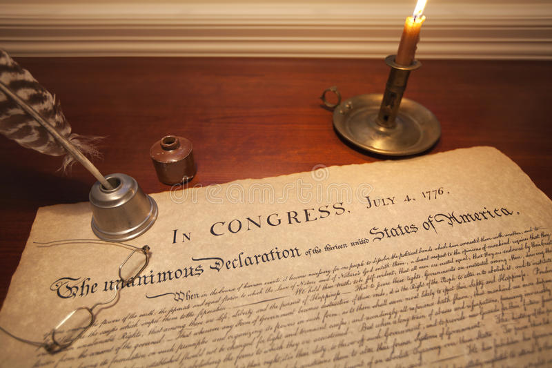 Declaration of Independence with glasses, quill pen and candle royalty free stock image