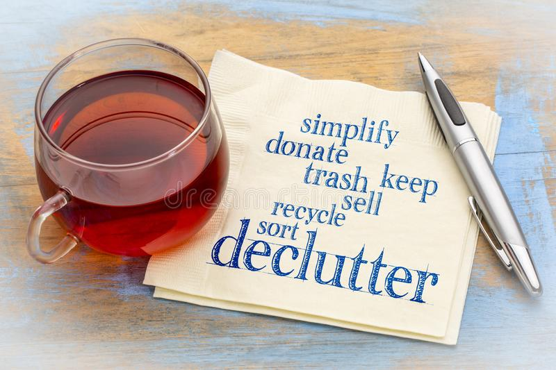 Declutter and simplify word cloud on napkin. Declutter and simplify word cloud on a napkin with a cup of tea stock photography