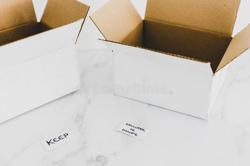 Decluttering concept, storage boxes to sort between objects to keep and those to declutter or donate with labels. Decluttering and tidying up conceptual still stock photography