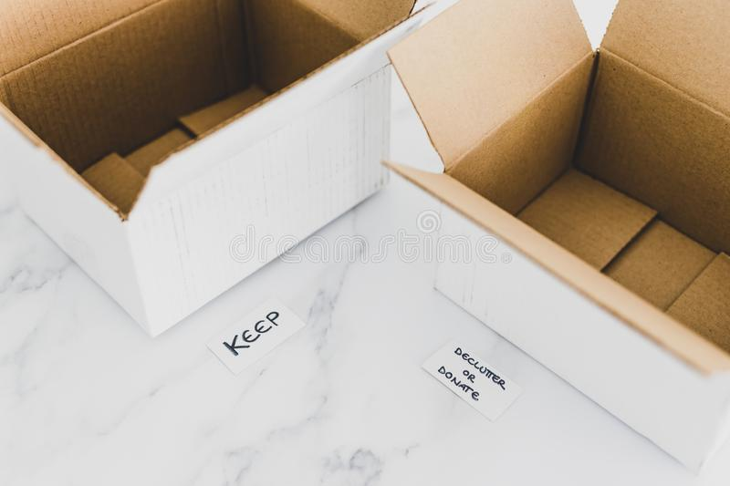 Decluttering concept, storage boxes to sort between objects to keep and those to declutter or donate with labels. Decluttering and tidying up conceptual still stock photo