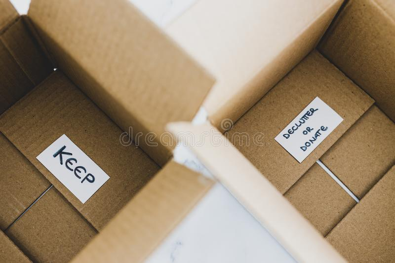Decluttering concept, storage boxes to sort between objects to keep and those to declutter or donate with labels. Decluttering and tidying up conceptual still stock photos