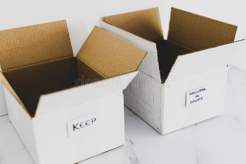 Decluttering concept, storage boxes to sort between objects to keep and those to declutter or donate with labels. Decluttering and tidying up conceptual still royalty free stock image