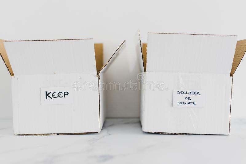Decluttering concept, storage boxes to sort between objects to keep and those to declutter or donate with labels. Decluttering and tidying up conceptual still stock image