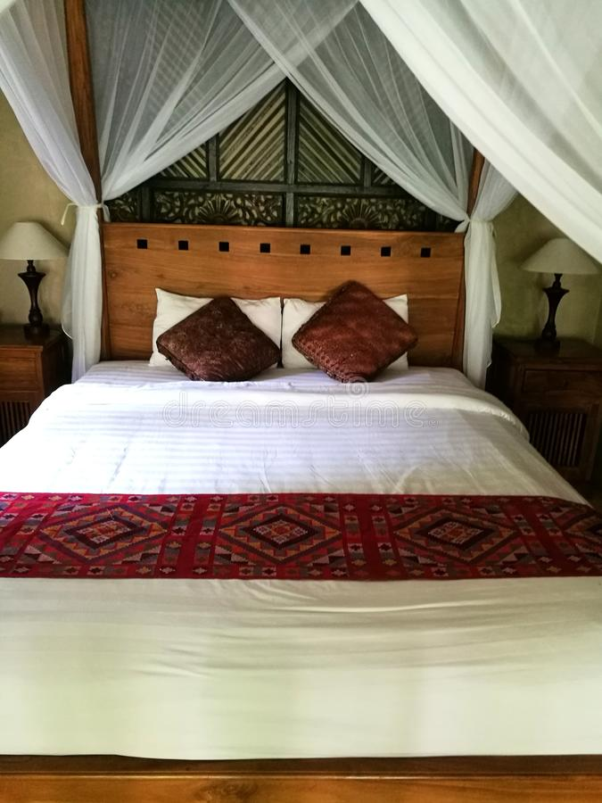 Deco della stanza del letto di stile di balinese nell'hotel di località di soggiorno di Bali immagine stock