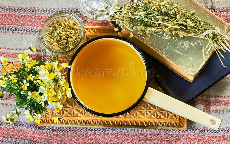Decoction of field viola arvensis or pansy plant with bouquet of fresh flowers and bunch of dried. One nearby on old pharmaceutical books, flat lay, top view royalty free stock images