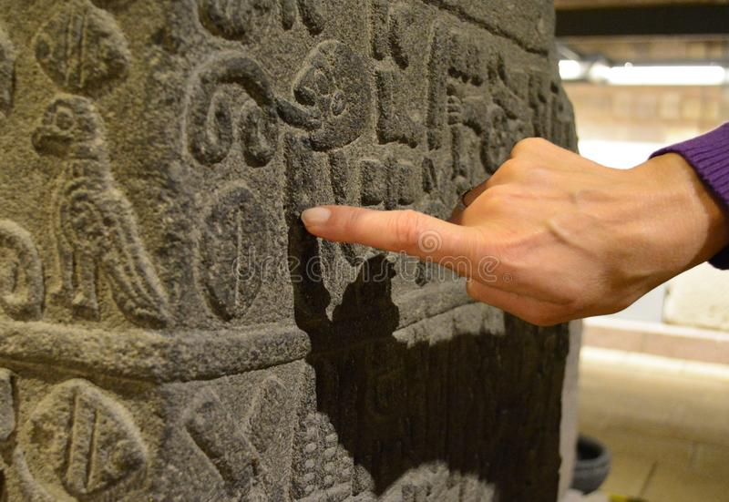 Decoding ancient text. Which belongs to an Ancient Anatolian civilization, the finger pointing to it shows importance of older textsn n stock photography