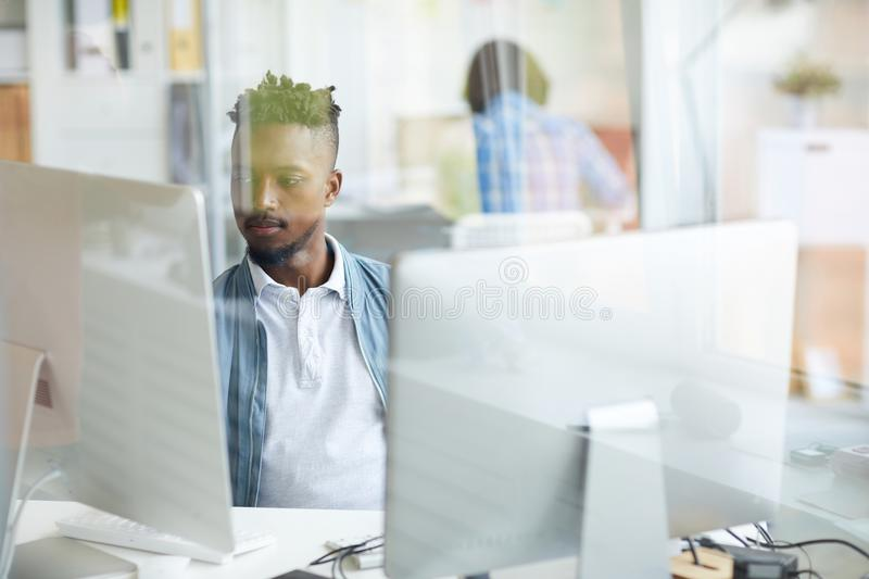 Decoding data. Serious guy concentrating on studying or decoding new data while sitting in front of computer monitors royalty free stock photos