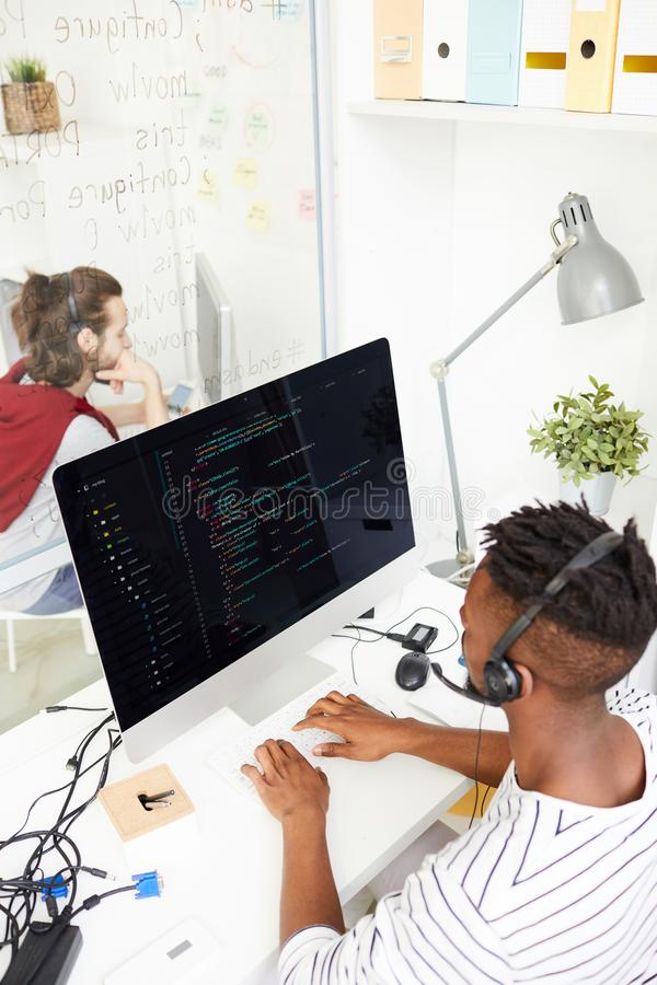 Decoding software. Contemporary programmer in headset analyzing or decoding data in computer and talking to clients in office royalty free stock images