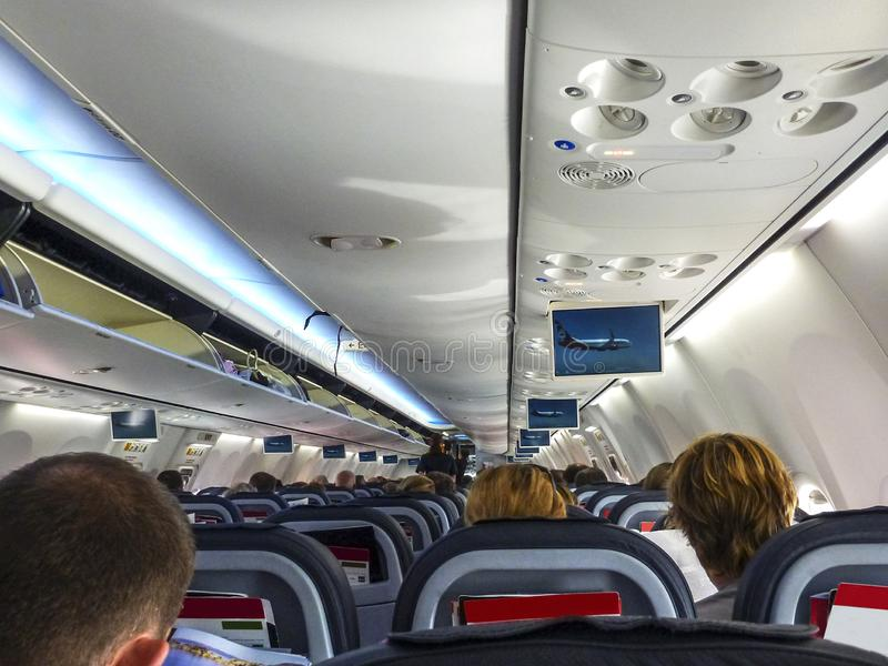 Decollo interno dell'aeroplano con i passeggeri messi e vista di prospettiva dei sedili e delle spese generali tutti fotografia stock
