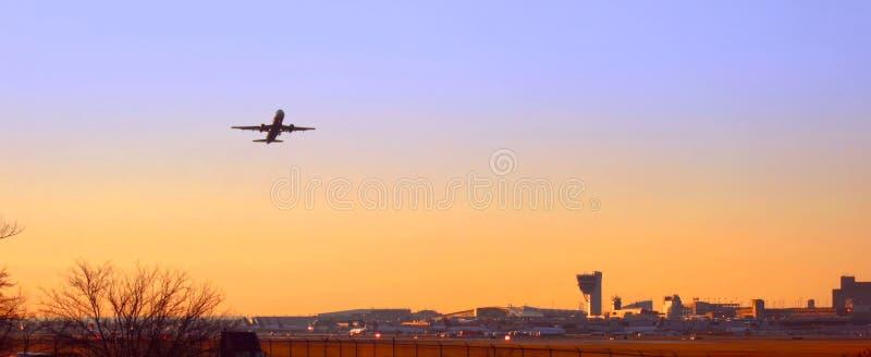 Decollo piano al tramonto all'aeroporto di Filadelfia fotografia stock