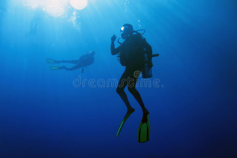 Decompressing after dive. A scuba diver decompressing after dive. Surrounding waters are serene and penetrated by sun beams royalty free stock image
