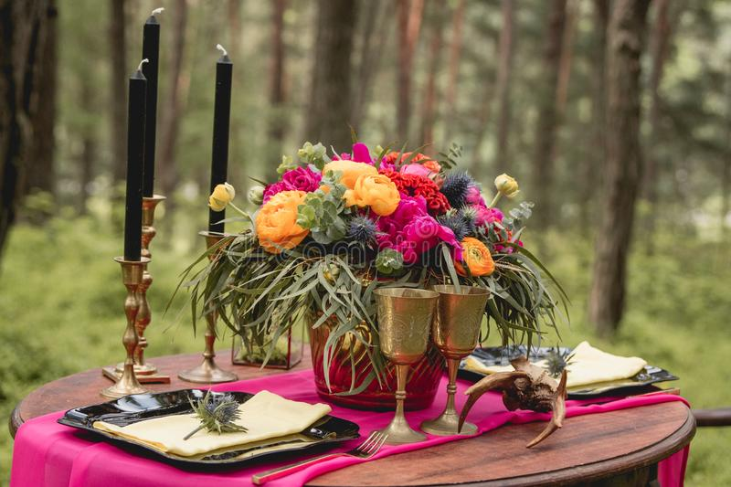 Decor. Details. Composition. Wedding decorations. On the wooden table in the woods there is a flower arrangement with royalty free stock photography