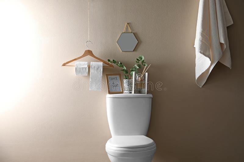 Decor elements, necessities and toilet bowl near beige wall. Bathroom. Interior stock image