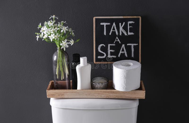 Decor elements, necessities and toilet bowl near black wall. Bathroom. Interior stock images